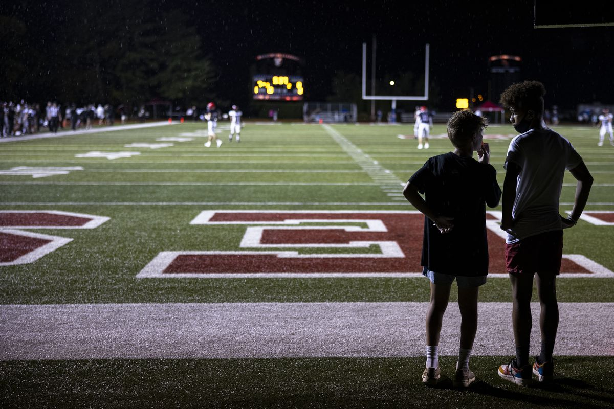 Two teenage boys watch stand at the back of the end-zone of a high school football field.