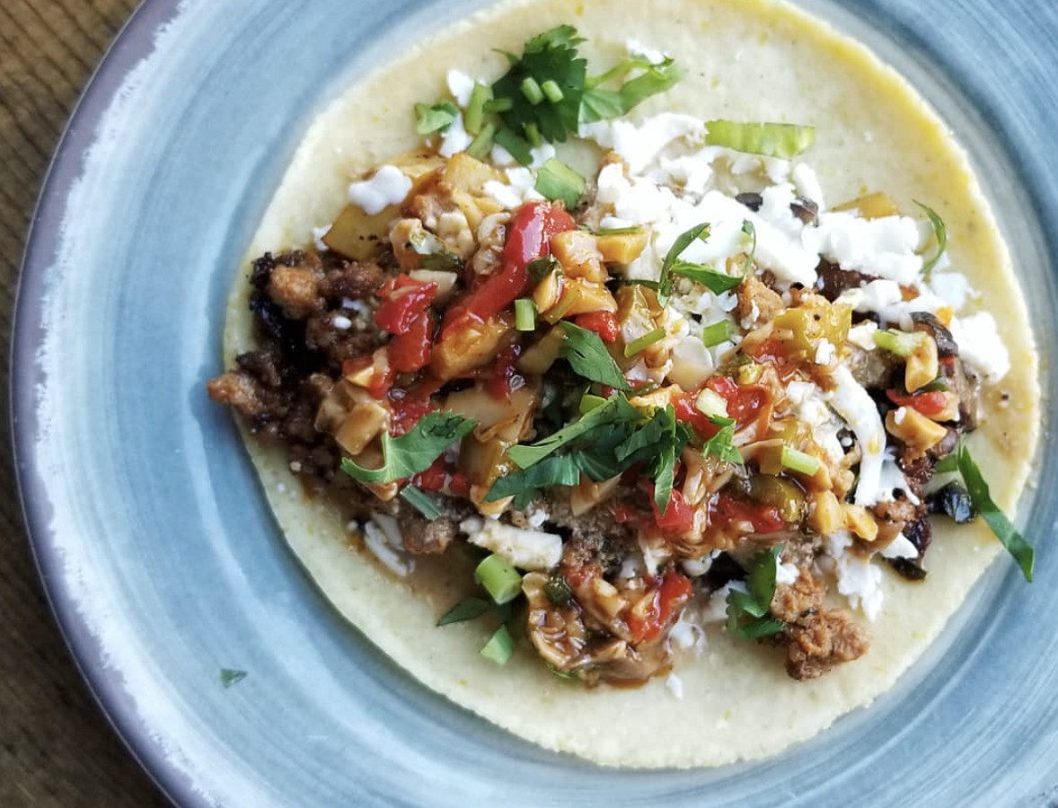 A chorizo and potato taco topped with cotija cheese, asparagus, and pickled mushroom salsa on a light blue plate