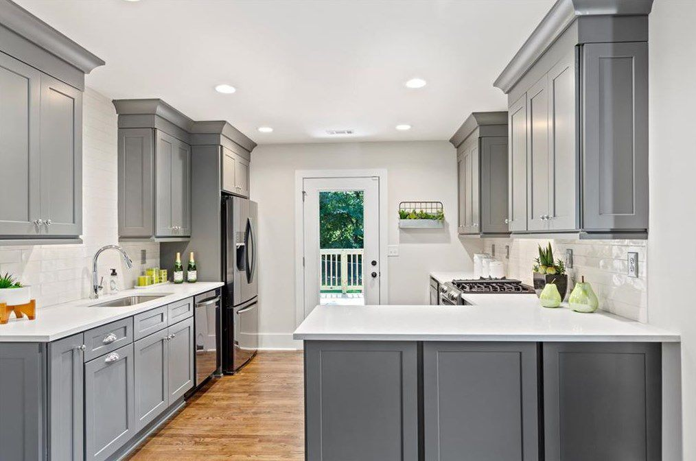 A large white kitchen with gray cabinetry.