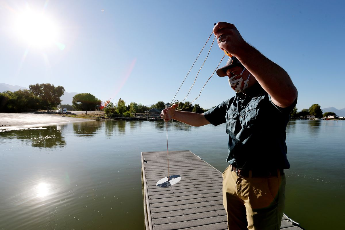 Ryan Van Goethem of SePro demonstrates the use of a Secchi disk to measure the water clarity as the company works to treat an algal bloom at Utah Lake on Friday, Sept. 4, 2020.