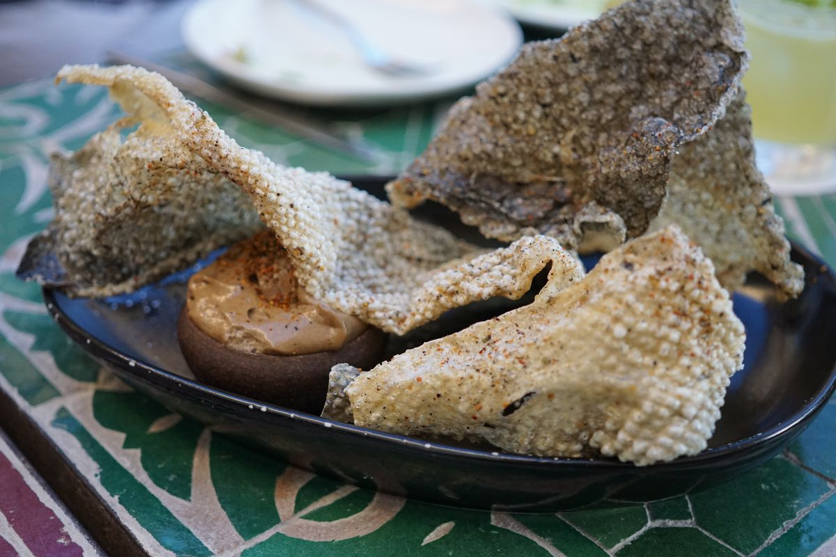 Salmon skin chicharrones on a dark plate with ornate table.