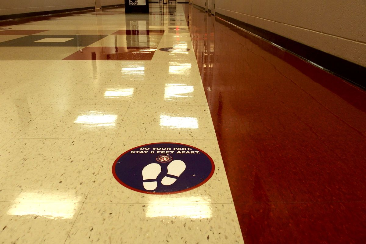 A sticker urging social distancing was placed in a school building hallway