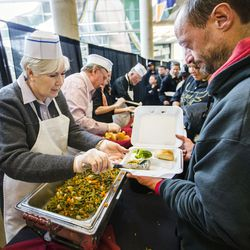Gail Miller and her husband, Kim Wilson, join Utah Jazz members and military members from Hill Air Force Base in serving a Thanksgiving meal to thousands of Salt Lake City's needy and homeless at EnergySolutions Arena in Salt Lake City on Nov. 25, 2014,