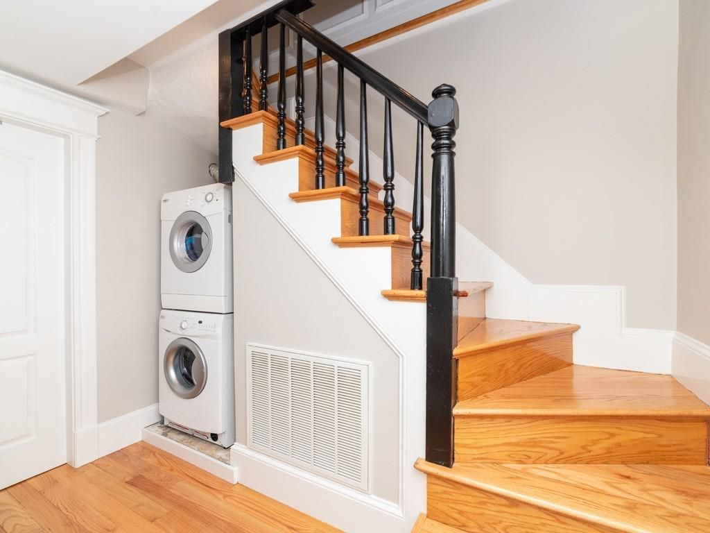 A squat stairwell with a washer-dryer stacked underneath it.