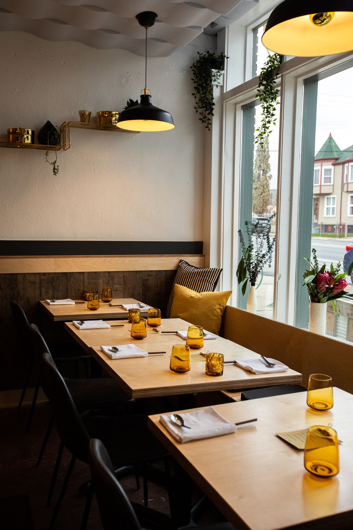Four wooden tables are lined up with chairs and a banquette running along the window next to the front entrance at Mink.
