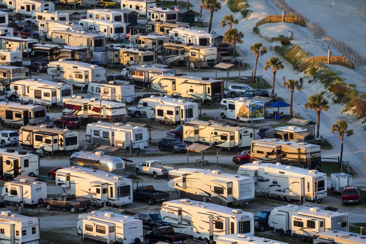 An aerial view of rows of RVs in a parking lot.