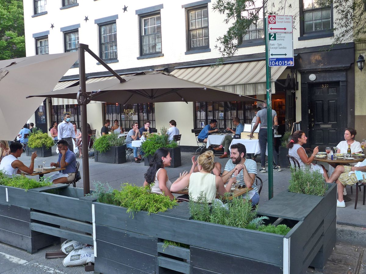 Outdoor seating area with tables and brown umbrellas right on the sidewalk.