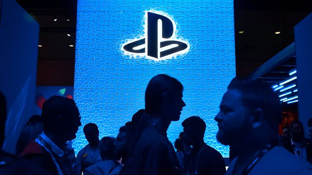 silhouetted people in front of a blue video board with the PlayStation logo