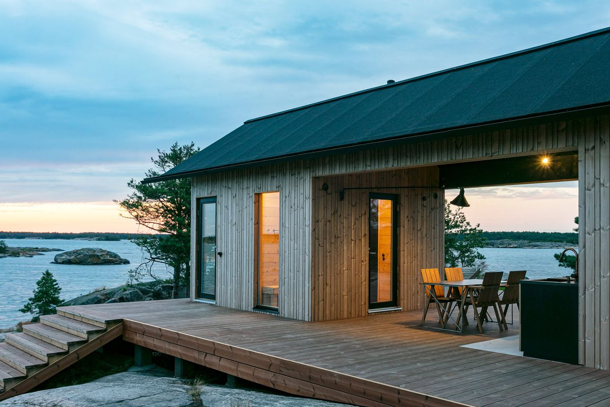 Wooden cabin with pitched roof and living area that opens out onto a wooden deck.