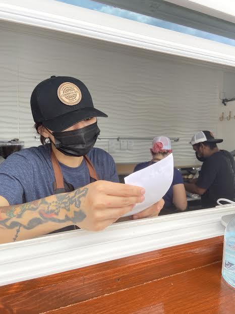 Order taker and cashier at Cubanos ATL in Sandy Springs, GA reading filled out menu sheet