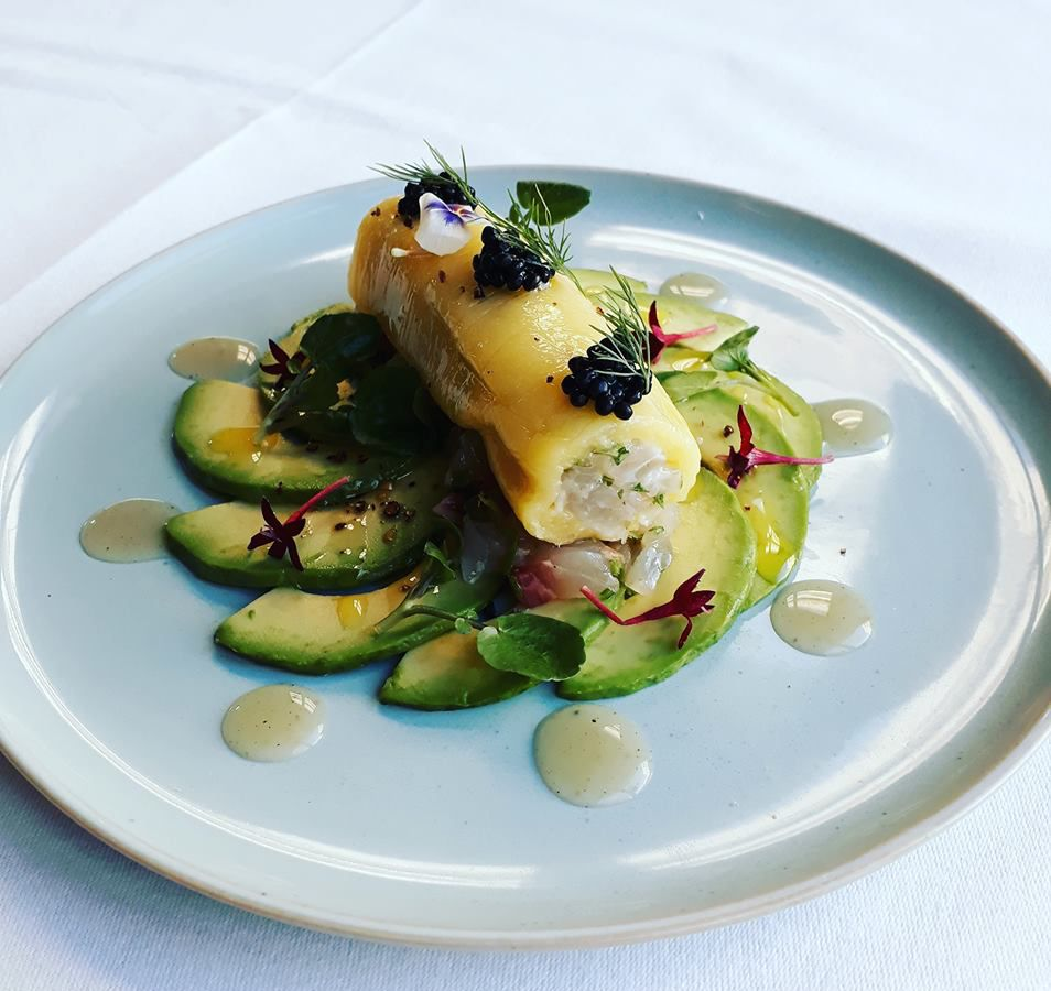 A tube of mango is filled with sea bream tartare, resting on a fan of avocado slices on a glossy plate on a neutral background
