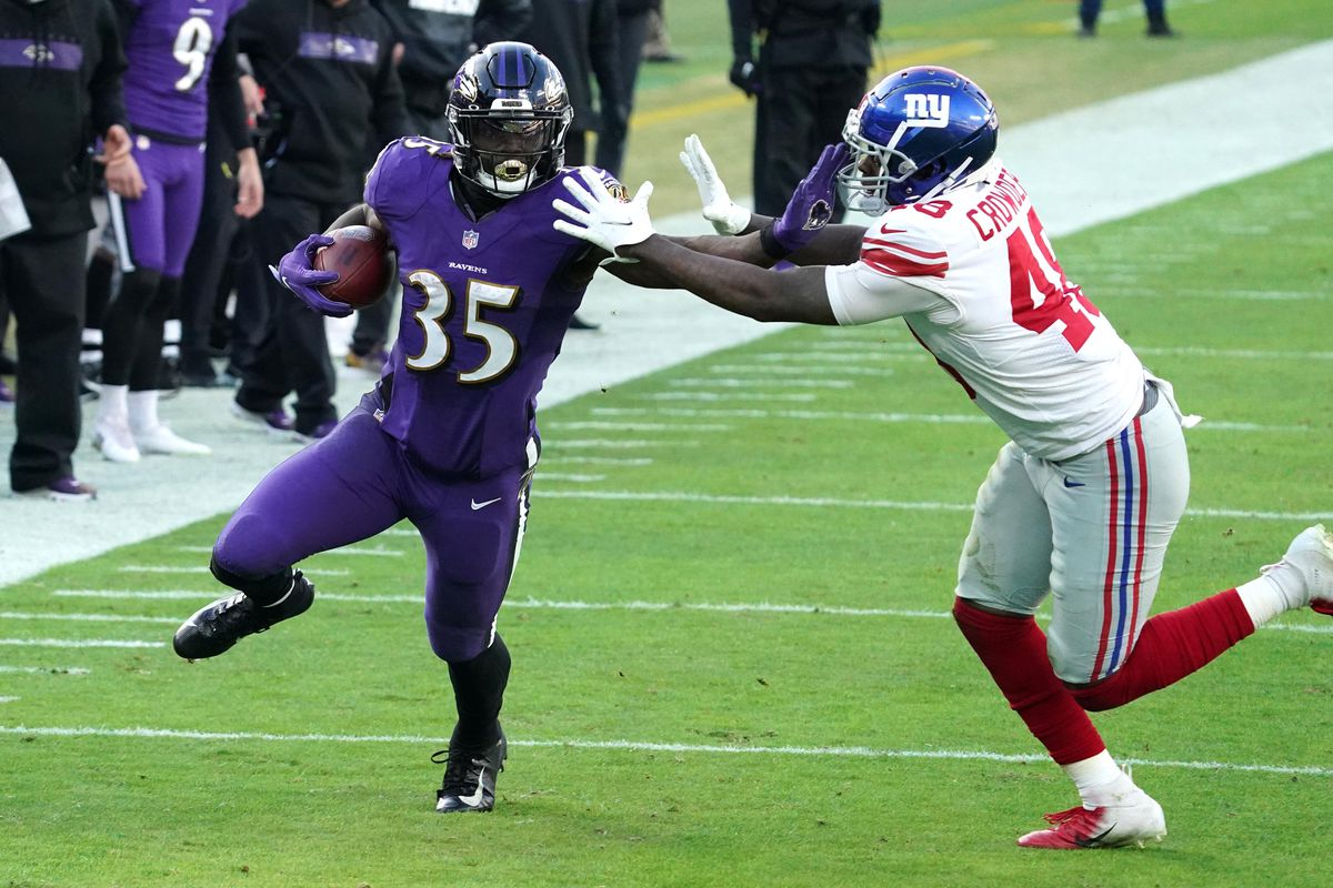 Baltimore Ravens running back Gus Edwards (35) runs for a fourth quarter gain defended by New York Giants linebacker Tae Crowder (48) at M&T Bank Stadium.