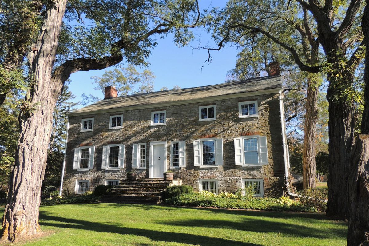 Colonial-style stone two-story house with shuttered windows and steps leading to front door on lawn surrounded by large trees.
