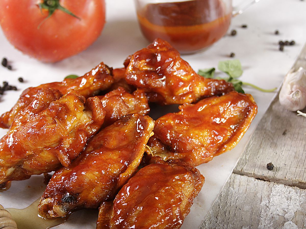 Wings are piled on a cutting board and slathered in red sauce.
