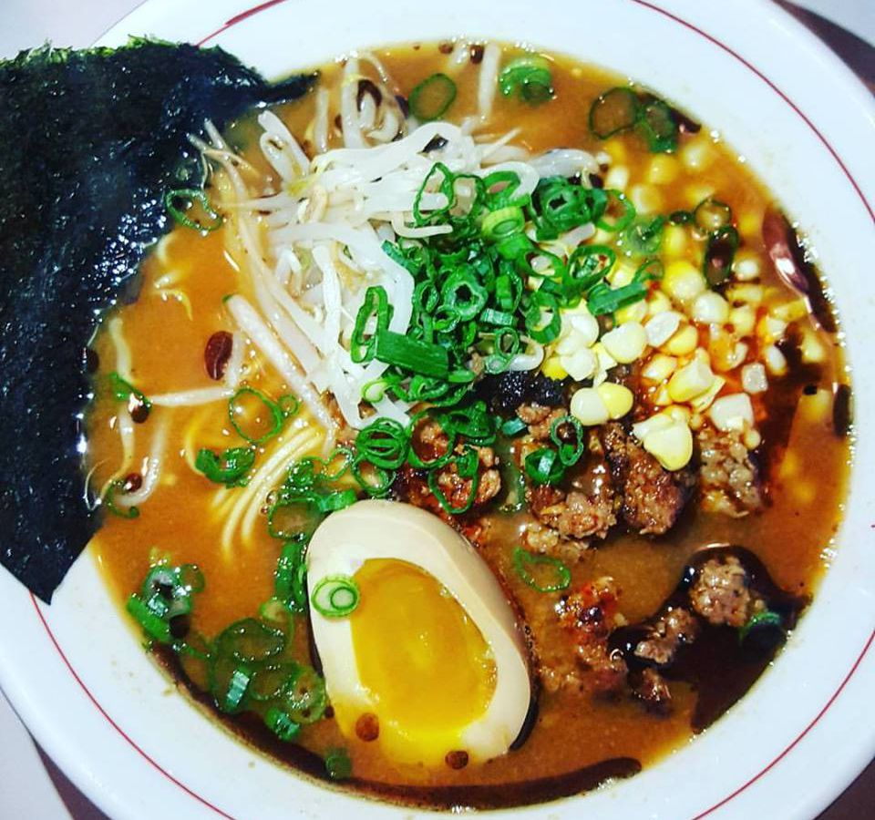 A large bowl of ramen shows broth filled with meat, greens, sprouts, corn, and a soft egg