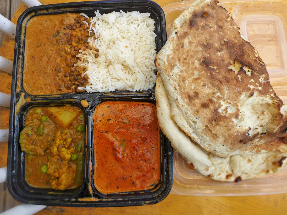 A plastic tray with three dishes, rice, and a folded naan.