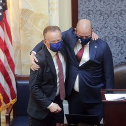 Senate President Stuart Adams, R-Layton, left, hugs Dan Hemmert, director of the Governor's Office of Economic Development, right, after Adams was sworn in during the first day of the 2021 general legislative session in the Senate chamber at the Capitol in Salt Lake City on Tuesday, Jan. 19, 2021.