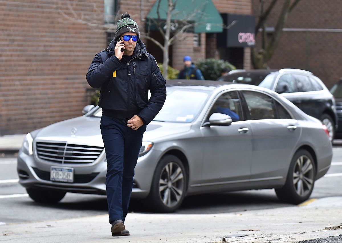 Bradley Cooper walking outside in a green-and-gray Eagles beanie