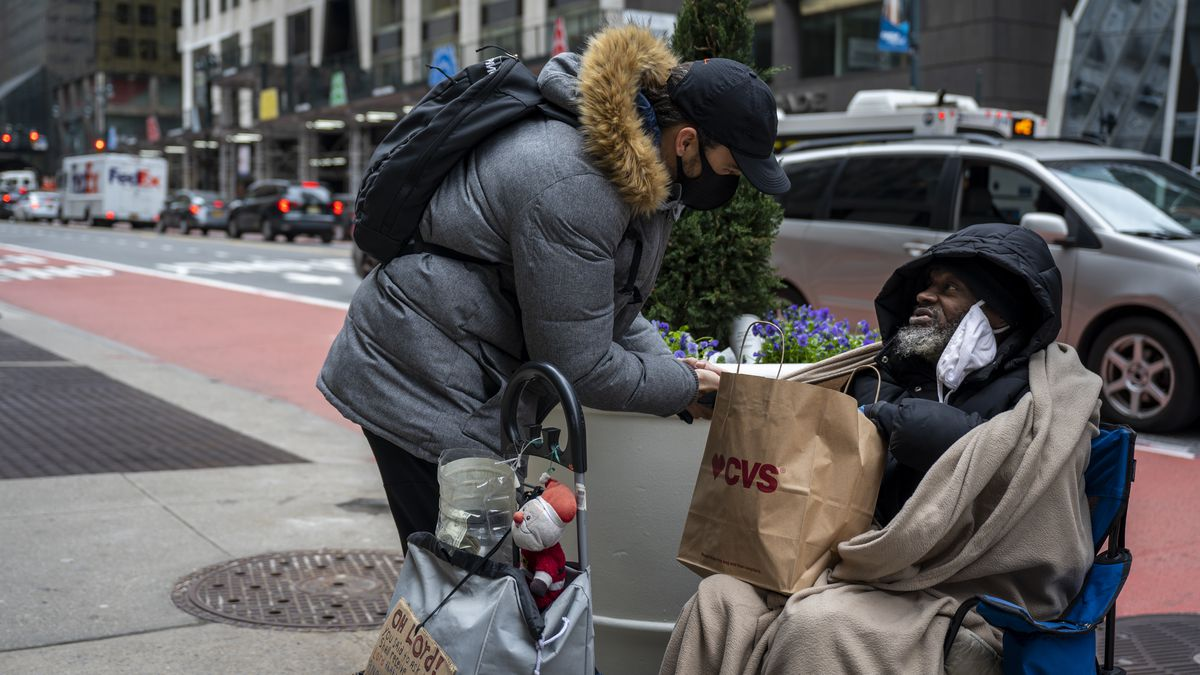 A passerby hands Anthony Lewis a bag filled with sandwiches and potato chips.