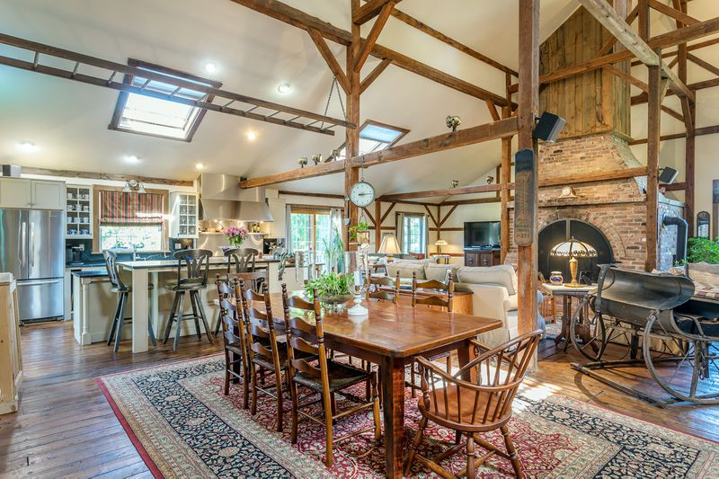 On the other side of the brick fireplace sits an open floorplan with kitchen, dining room table, and skylights.