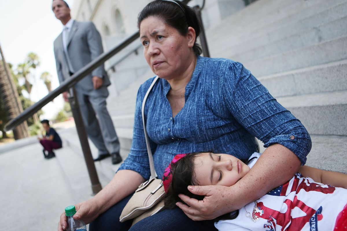 Ariely Murrilo (BOTTOM), a U.S. citizen, rests with her grandmother Lucresia Argueta, a U.S. resident, at the launch of the 'TPS Journey for Justice Caravan' outside City Hall on August 17, 2018 in Los Angeles, California. Ariely's mother is a TPS recipie