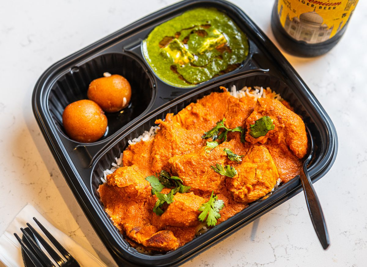 A black to-go container is full of butter chicken in a brick-red gravy and side compartments full of green palak paneer and orb-shaped gulab jamun.