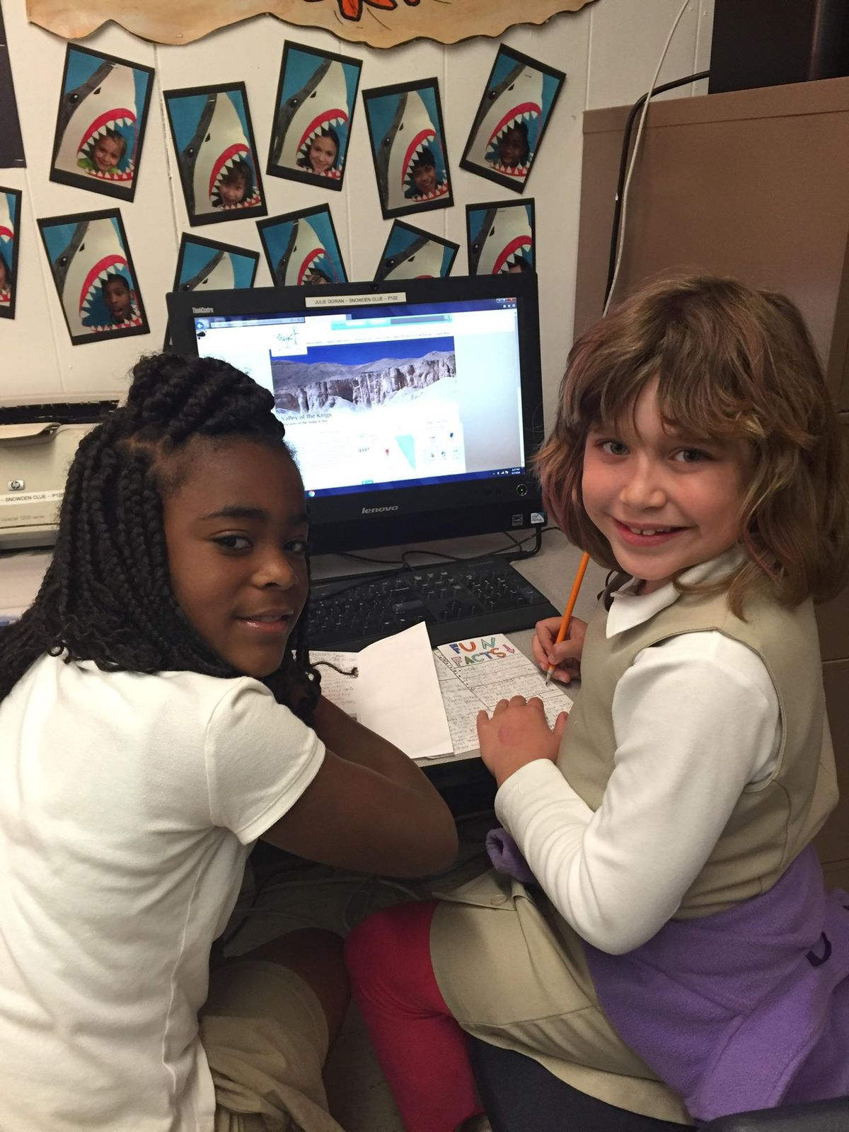 """From left: Students India Turner and Nina Crespo do online research for an ancient Egypt """"travel guide"""" during a CLUE class at Snowden School in Memphis."""