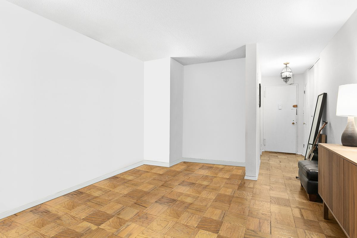 A living room with hardwood floors and white walls.