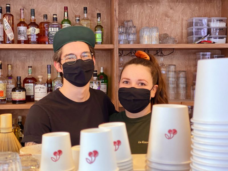 Man and women wearing face mask in cafe