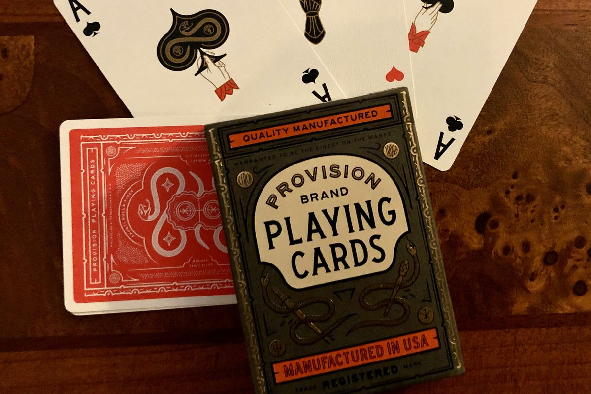 Three fanned aces and a pack of Provision paying cards.