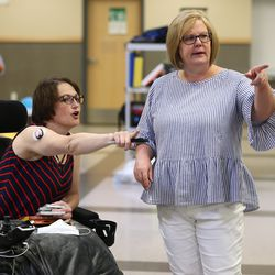 Ravien Parsons and Principal Diana Brantley talk about placement of items as they work to organize yard sale items at Summit Academy in Bluffdale on Friday, June 19, 2020. Parsons has experienced a sudden disability after being diagnosed with stiff-person syndrome. The charter school where she teaches is holding the fundraiser to help her buy a wheelchair-accessible van so she can continue to work and more effectively live her life.