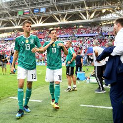 Özil begins to take off his jersey as he heads to the tunnel just behind Thomas Müller. Andreas Köpke can be seen directly behind him.