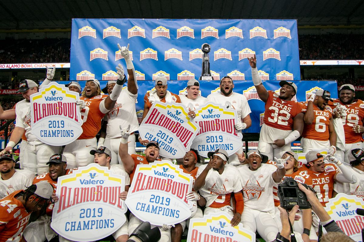 Texas Longhorns celebrate on the trophy podium after winning the Alamo Bowl game against the Utah Utes on December 31, 2019 at the Alamodome in San Antonio, Texas.