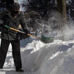 Jason Topping shovels snow in the Edgewater neighborhood, Tuesday morning, Feb. 16, 2021, after a snowstorm dumped over a foot of snow in Chicago starting Sunday night. Snow is expected to continue to fall until Tuesday night.
