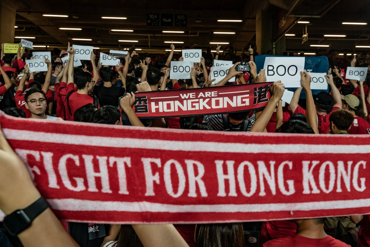 """Pro-democracy protesters in Hong Kong raise their fists and hold up banners that read """"Boo,"""" """"We are Hong Kong"""" and """"Fight for Hong Kong."""""""