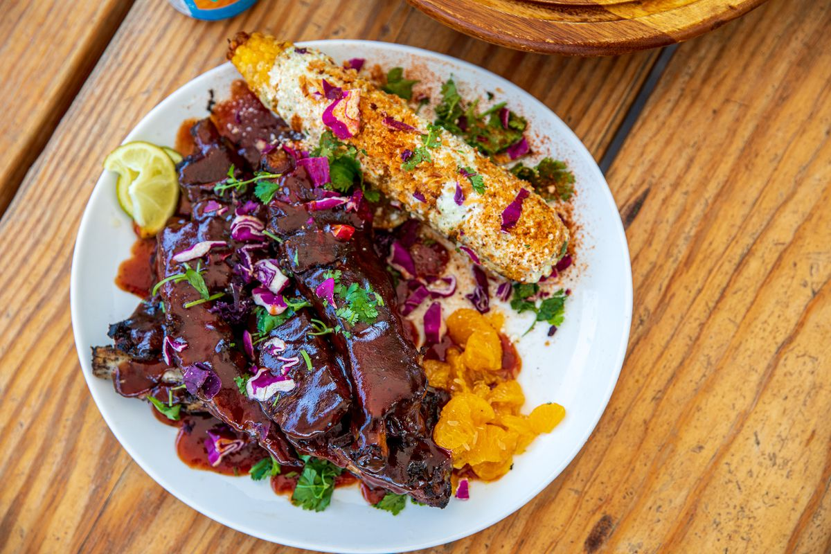 The ribs are on a plate slathered in a dark guava barbecue sauce with grilled corn covered in cheese and sprinkled with purple cabbage slivers and cilantro.