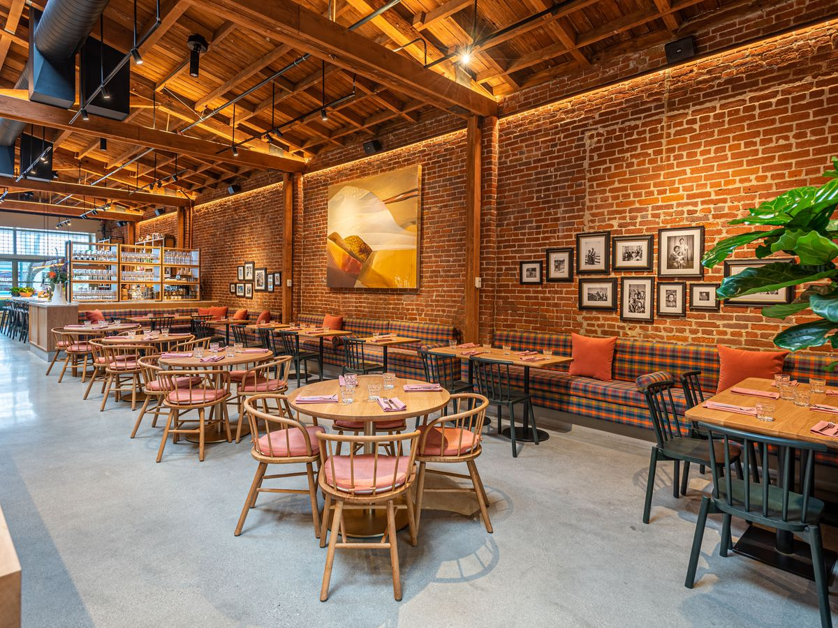 Round four-top tables and brick walls inside a new restaurant with tall ceilings.