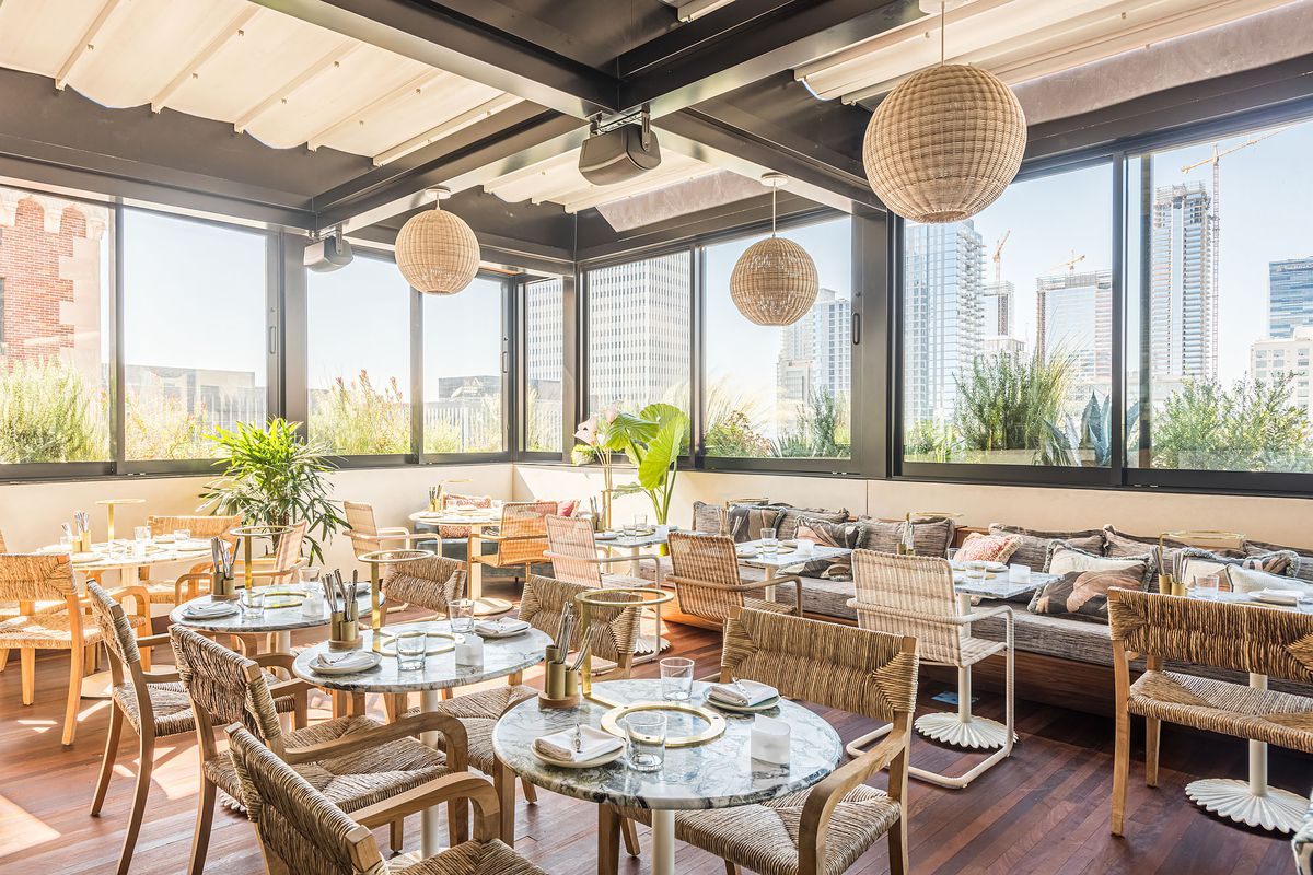 A corner rooftop restaurant with sunlight streaming in.