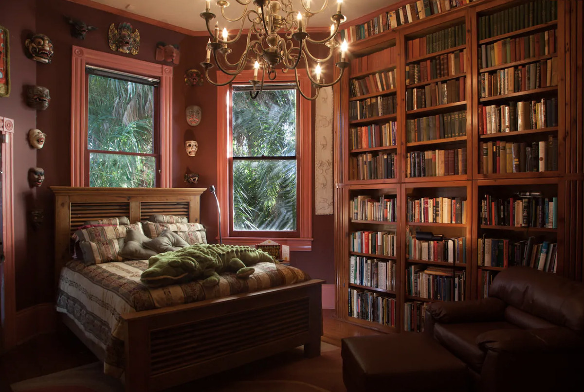 A room with floor to ceiling bookshelves, a chandelier and a bed, plus windows overlooking ferns and greenery
