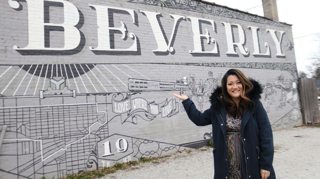 """Ji Suk Yi in front of a Beverly mural with the neighborhood's motto, """"Love where you live."""" 