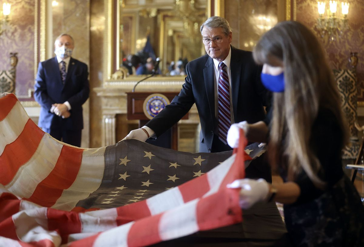 Jan Benson, center, helps unfold the original 45-star flag that flew over the U.S. Capitol when Utah became the 45th state in 1896 as he presents it to the state at the Capitol in Salt Lake City on Tuesday, May 11, 2021. It will be displayed on the first floor of the Utah Capitol.