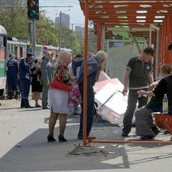 People assist injured after explosion in Dnipropetrovsk, Ukraine, Friday, April 27, 2012.  Ukraine officials say dozens of people including schoolchildren were injured in four blasts in eastern city.