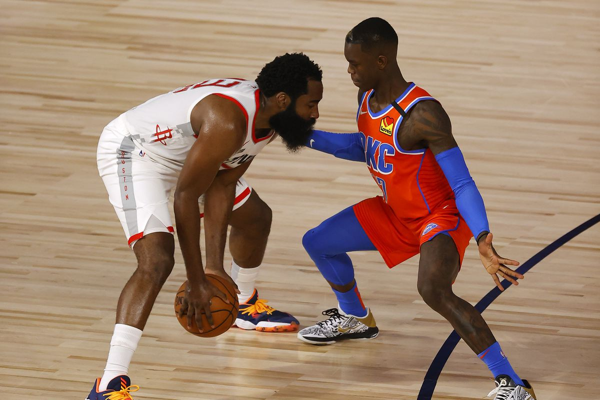 Dennis Schroder of the Oklahoma City Thunder defends against James Harden of the Houston Rockets during the second quarter in Game Three of the Western Conference First Round during the 2020 NBA Playoffs at The Field House at ESPN Wide World Of Sports Complex on August 22, 2020 in Lake Buena Vista, Florida.