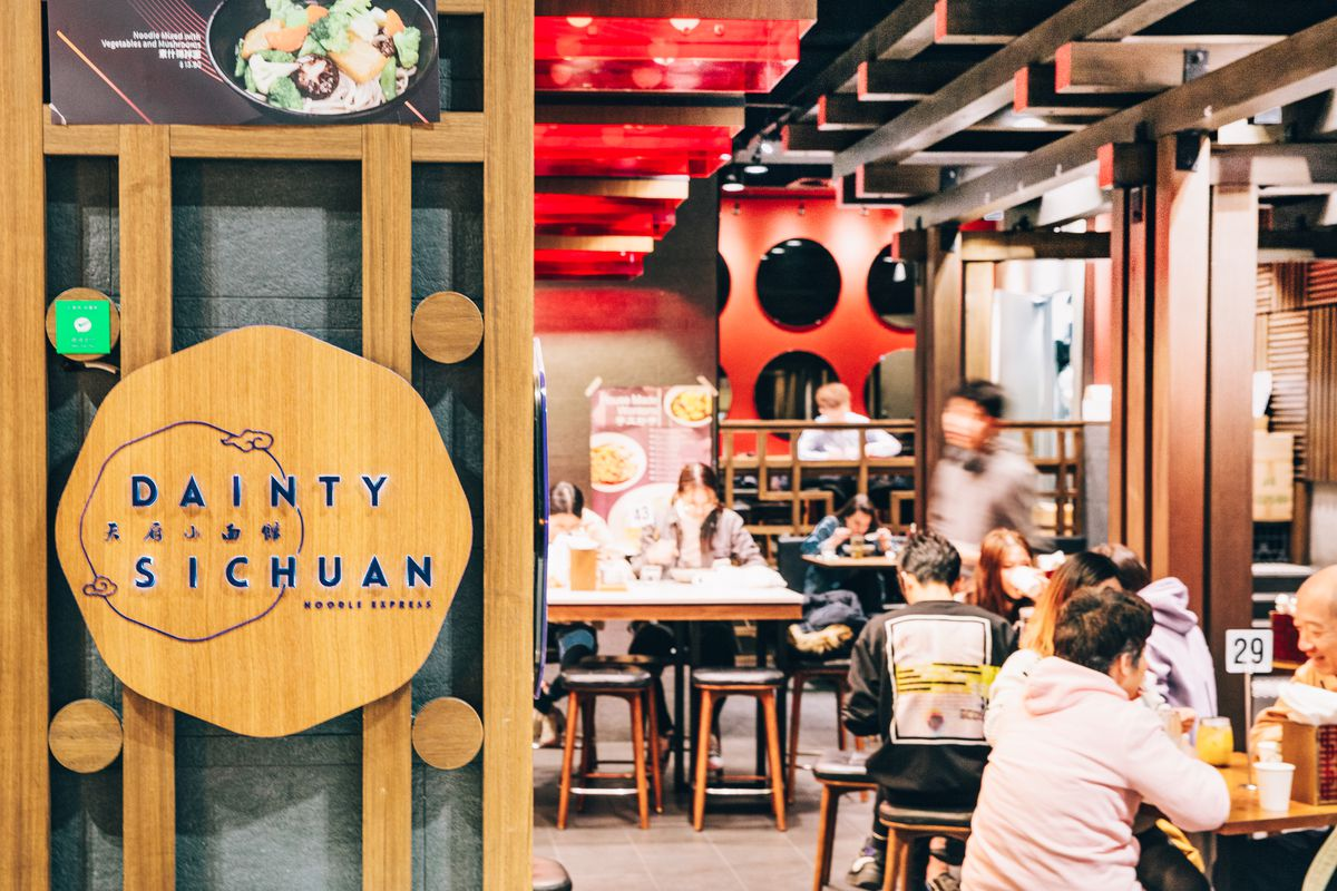 A round sign for Dainty Sichuan; behind it, several young people sit at restaurant tables.