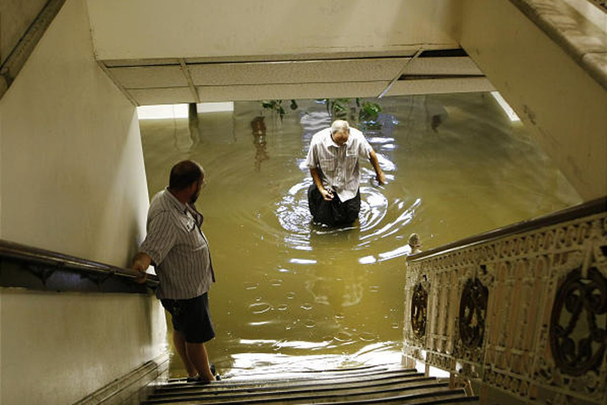 Louisville library worker Joe Brady, left, looks on as co-worker William Cantelli wades through floodwaters.
