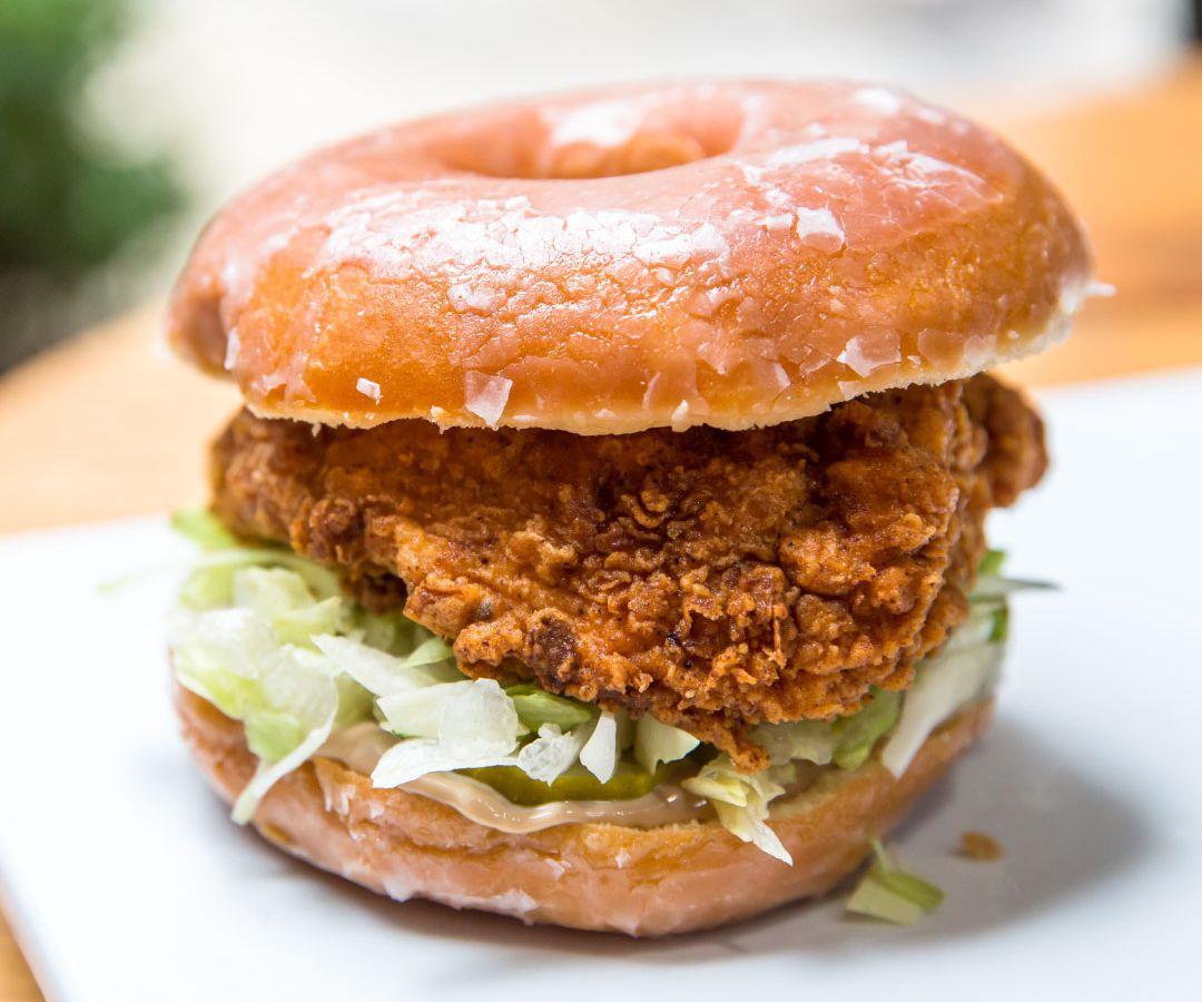 A fried chicken sandwich served on a doughnut bun.