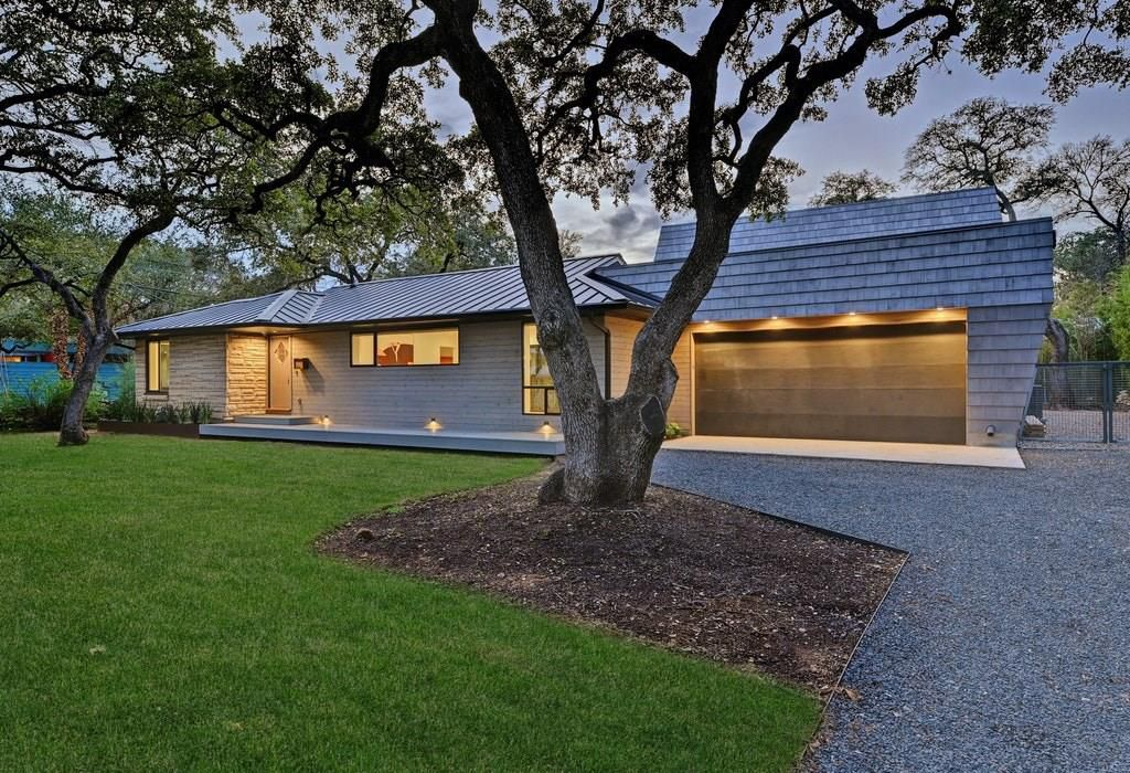 A twilight photo of the front of a limestone ranch style home that has been renovated with a wood-shingled, two-story addition on top of and behind the garage. there are a couple of trees surrounded by grass in the foreground and a gravel driveway and side yard.