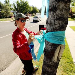 Connie Engh joins with other community members tying ribbons and writing messages to the Rackley family and first responders of the murder-suicide along Alta Canyon Drive in Sandy on Saturday, June 10, 2017.