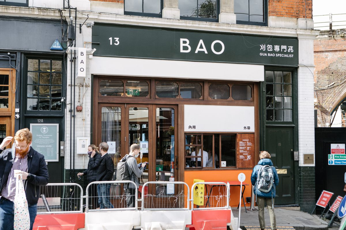 The exterior of Bao's restaurant in Borough Market, with BAO in white capital letters over a takeaway window and hatch. Customers in masks stand in the street outside
