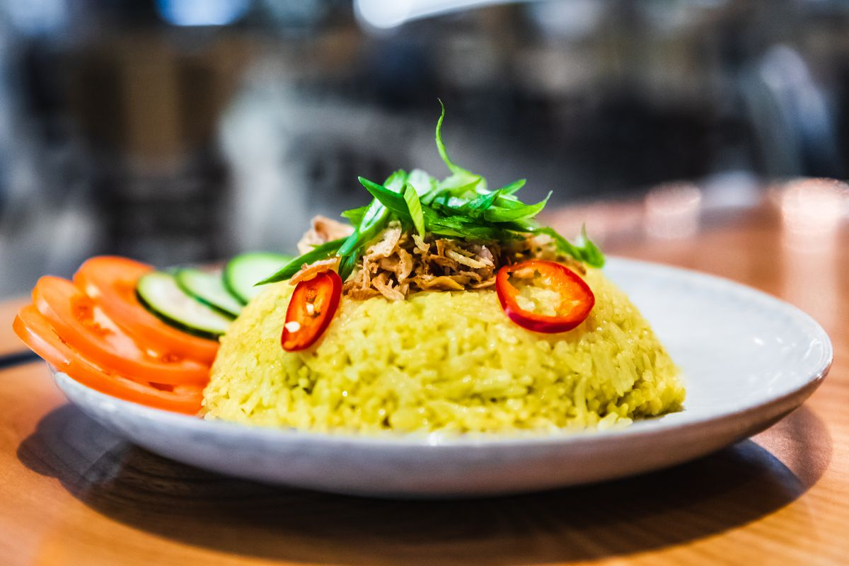 A white plate holds a mound of yellow rice beside slices of tomato and cucumber.